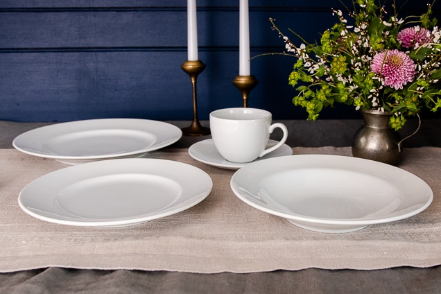 A variety white Williams Sonoma Brasserie All-White Dinnerware on a certain kitchen table.