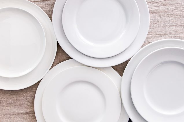 A lead down sight of four different dinnerware discs on a fabric table cloth.