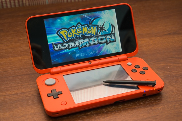 An lime brand new Nintendo 2DS XL on a wood stand, open and fired up to display the PokeMon UltraMoon introduction display.