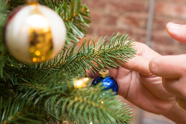 A up close of people putting an ornament on all of our choice for best unnatural Christmas forest.