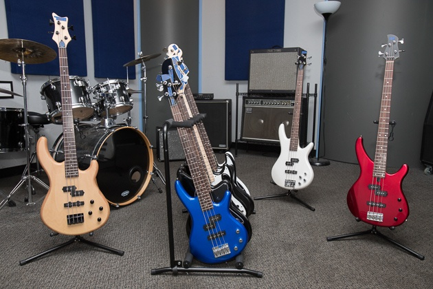 Seven muskie instruments different colours and styles established in an area with a drumset and amplifiers.