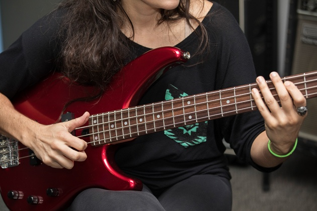 A individual taking part in a red yamaha trbx174 perch guitar.