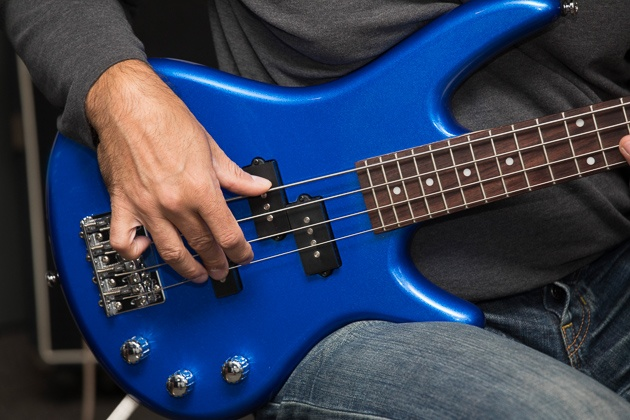 A person using a bluish ibanez mikro.