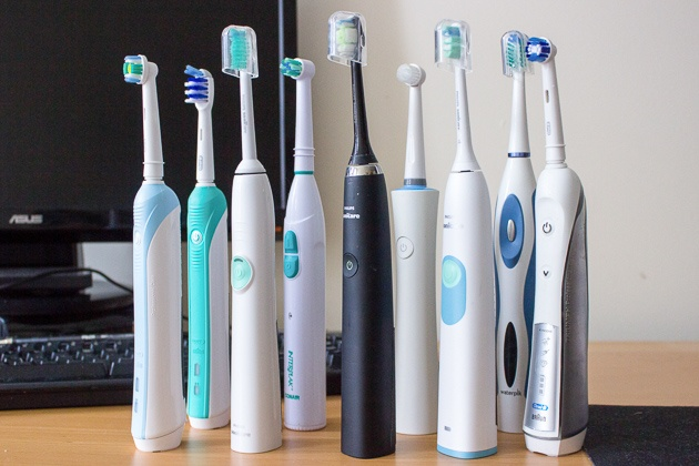 Nine electricity toothbrushes of several companies and types standing.