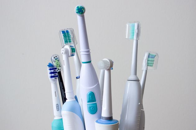 Eight electric power toothbrushes of various models and brands.