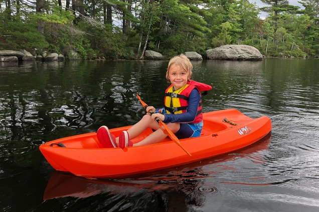 A toddler paddling in a red boat on a water. The kid is dressed in a life dress and smile at the camera.