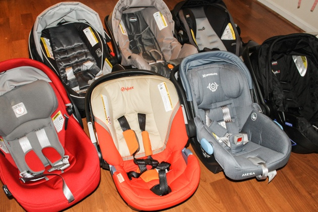 Seven toddler carseats you sit on a wood surface.