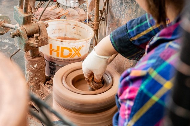A particular person creating a wheel in a ceramics mold.