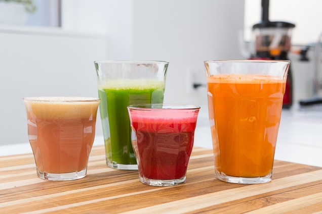 Four glasses of juice from different fruits and veggies.