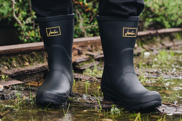 a set of dark-colored Kamik Lars rainwater boots in a grassy mess.