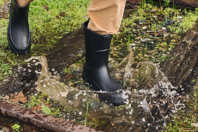 A pair of black colored Crocs Men's AllCast rainwater shoe remaining run in a grassy plant.