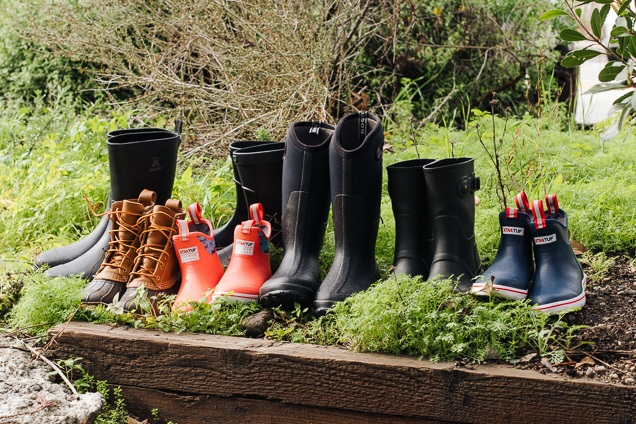 Seven couples of rainboots varying color and shapes arranged in lawn.
