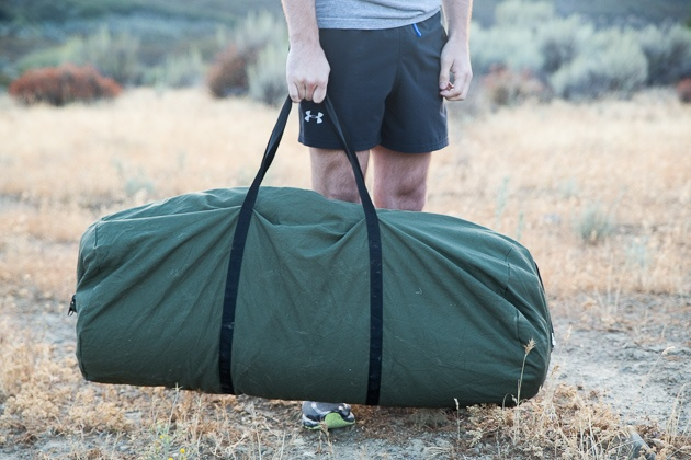 A man carrying the Slumberjack state escort 20 napping case with the high alternative duffel bag.