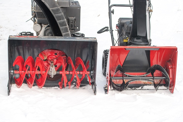 Two purple and dark-colored snow blowers outside in the snow.
