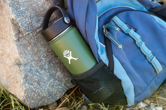 The Hydro Flask 18oz spacious orifice water system sprayer inside hauling pouch of a backpack tilt against a stone.